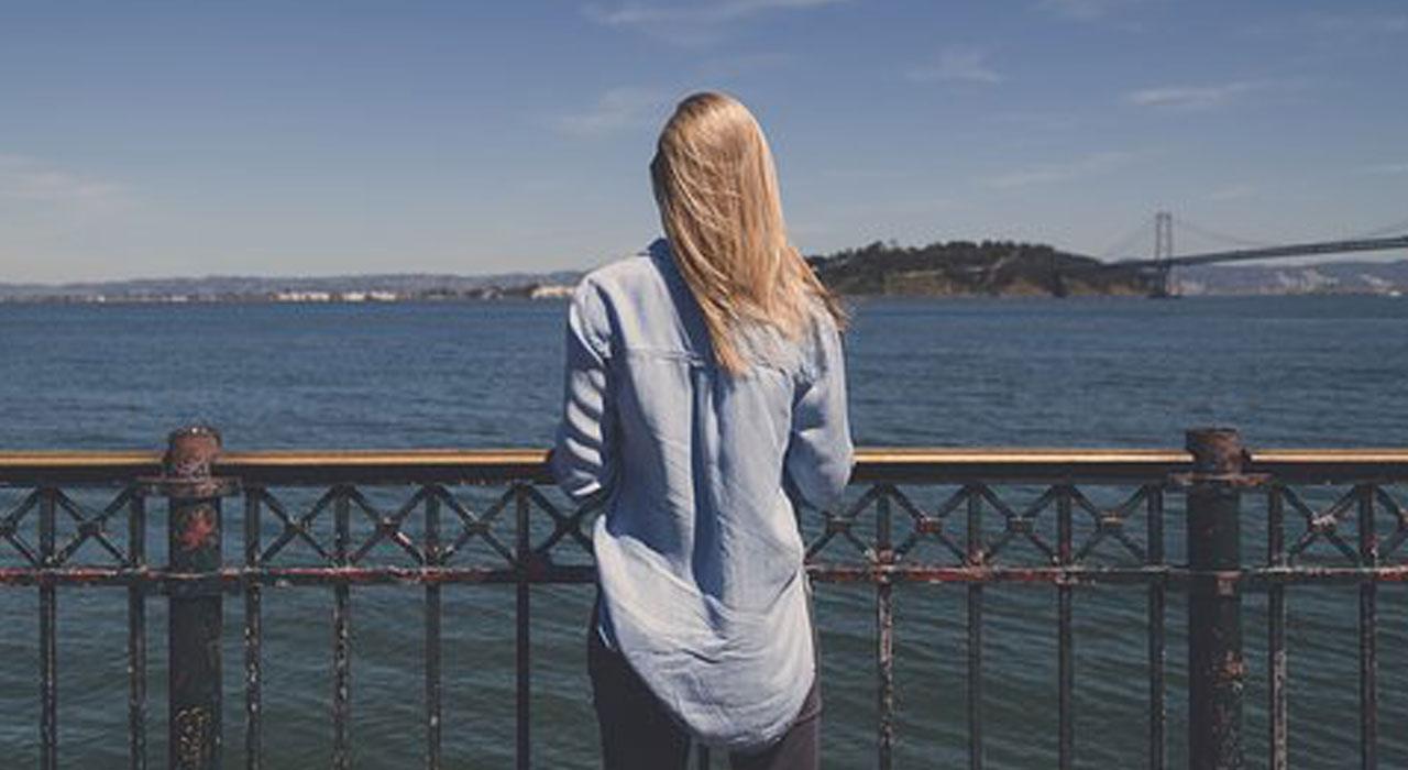 海を眺めている女性の後姿